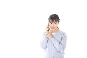 スマホを使う若い女子学生の写真素材 [FYI04716658]