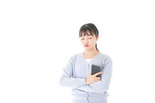 スマホを使う若い女子学生の写真素材 [FYI04716659]