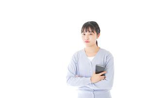 スマホを使う若い女子学生の写真素材 [FYI04716660]