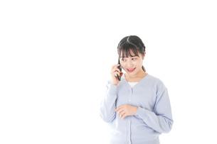 スマホを使う若い女子学生の写真素材 [FYI04716662]