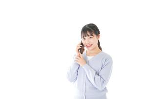 スマホを使う若い女子学生の写真素材 [FYI04716663]