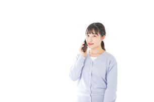 スマホを使う若い女子学生の写真素材 [FYI04716664]