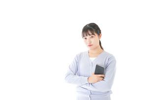 スマホを使う若い女子学生の写真素材 [FYI04716665]