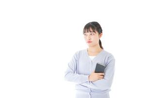 スマホを使う若い女子学生の写真素材 [FYI04716666]