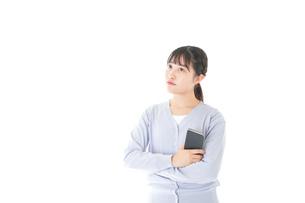 スマホを使う若い女子学生の写真素材 [FYI04716667]