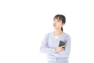スマホを使う若い女子学生の写真素材 [FYI04716668]