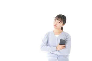 スマホを使う若い女子学生の写真素材 [FYI04716669]