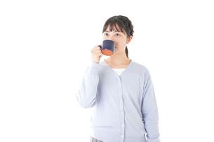 マグカップでコーヒーを飲む若い女性の写真素材 [FYI04716693]