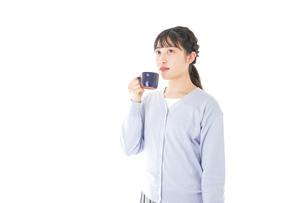 マグカップでコーヒーを飲む若い女性の写真素材 [FYI04716697]