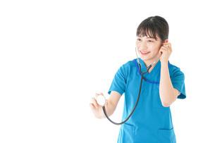 聴診器を使う笑顔の若いナースの写真素材 [FYI04716769]