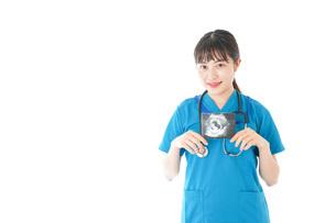 妊婦のエコー画像と笑顔の若いナースの写真素材 [FYI04716776]