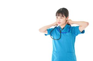 聴診器を使う笑顔の若いナースの写真素材 [FYI04716779]