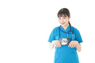 妊婦のエコー画像と笑顔の若いナースの写真素材 [FYI04716781]