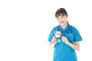 妊婦のエコー画像と笑顔の若いナースの写真素材 [FYI04716785]
