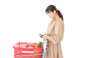 スーパーで食品の原産地を調べる若い女性の写真素材 [FYI04716909]