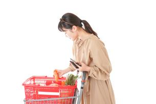 スーパーで食品の原産地を調べる若い女性の写真素材 [FYI04716911]
