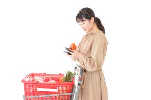 スーパーで食品の原産地を調べる若い女性の写真素材 [FYI04716912]