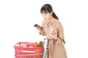 スーパーで食品の原産地を調べる若い女性の写真素材 [FYI04716913]