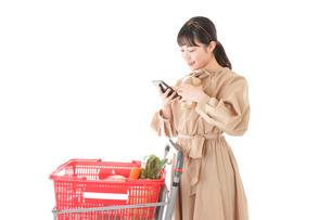 スーパーで食品の原産地を調べる若い女性の写真素材 [FYI04716914]