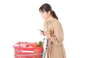 スーパーで食品の原産地を調べる若い女性の写真素材 [FYI04716915]