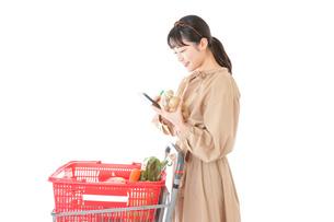 スーパーで食品の原産地を調べる若い女性の写真素材 [FYI04716916]