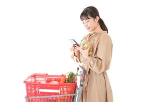 スーパーで食品の原産地を調べる若い女性の写真素材 [FYI04716918]