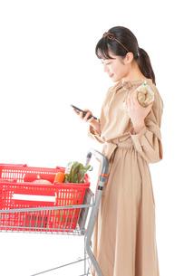 スーパーで食品の原産地を調べる若い女性の写真素材 [FYI04716919]