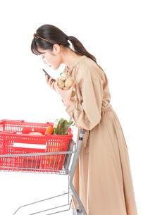 スーパーで食品の原産地を調べる若い女性の写真素材 [FYI04716920]