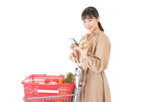 スーパーで食品の原産地を調べる若い女性の写真素材 [FYI04716921]