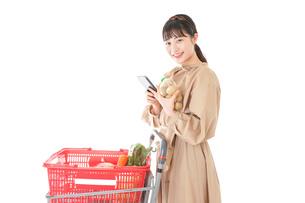 スーパーで食品の原産地を調べる若い女性の写真素材 [FYI04716922]