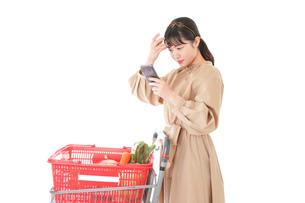 スーパーで食品の原産地を調べる若い女性の写真素材 [FYI04716923]