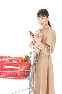 スーパーで食品の原産地を調べる若い女性の写真素材 [FYI04716925]