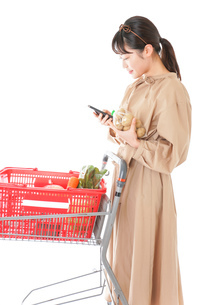 スーパーで食品の原産地を調べる若い女性の写真素材 [FYI04716926]