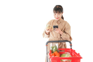 スーパーで食品の原産地を調べる若い女性の写真素材 [FYI04716927]