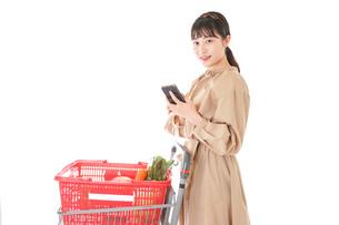 スーパーで食品の原産地を調べる若い女性の写真素材 [FYI04716928]
