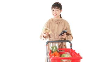 スーパーで食品の原産地を調べる若い女性の写真素材 [FYI04716935]