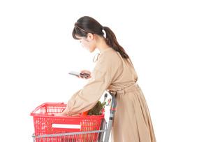 スーパーで食品の原産地を調べる若い女性の写真素材 [FYI04716936]