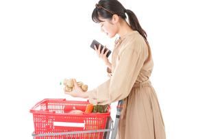 スーパーで食品の原産地を調べる若い女性の写真素材 [FYI04716937]