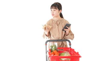 スーパーで食品の原産地を調べる若い女性の写真素材 [FYI04716941]
