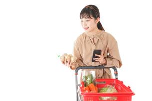 スーパーで食品の原産地を調べる若い女性の写真素材 [FYI04716942]
