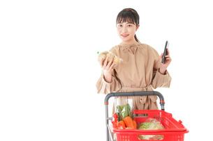 スーパーで食品の原産地を調べる若い女性の写真素材 [FYI04716943]