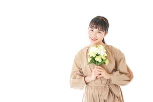 笑顔で花束を持つ若い女性の写真素材 [FYI04716992]