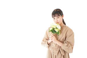 笑顔で花束を持つ若い女性の写真素材 [FYI04717004]