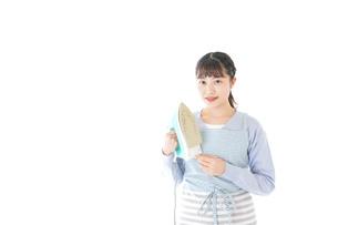 アイロン掛けをする若い主婦の写真素材 [FYI04717248]