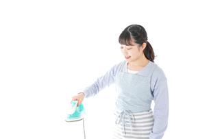 アイロン掛けをする若い主婦の写真素材 [FYI04717260]