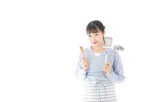 笑顔で料理をする若い主婦の写真素材 [FYI04717392]