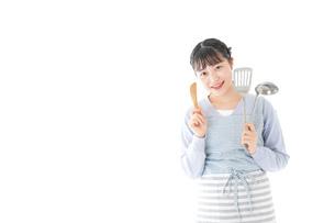 笑顔で料理をする若い主婦の写真素材 [FYI04717394]
