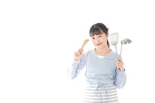 笑顔で料理をする若い主婦の写真素材 [FYI04717397]