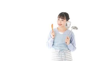 笑顔で料理をする若い主婦の写真素材 [FYI04717400]