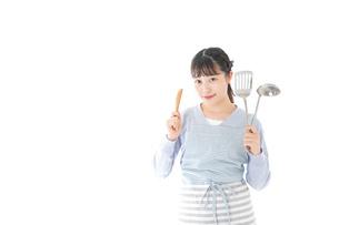 笑顔で料理をする若い主婦の写真素材 [FYI04717404]